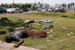 Bodies lay outside the south gate of Gaddafi's Bab al-Aziziya compound as rebels make the final push to flush Gaddafi's forces from the compound in Tripoli